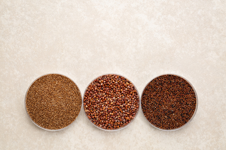 teff, quinoa and kaniwa gluten free grains in round bowls agains ceramic tile background, top view with a copy space