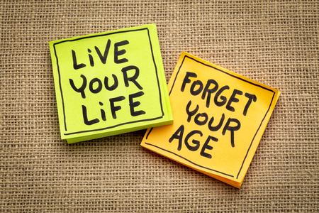 Live your life, forget your age - inspirational handwriting on sticky notes against burlap canvas Stok Fotoğraf