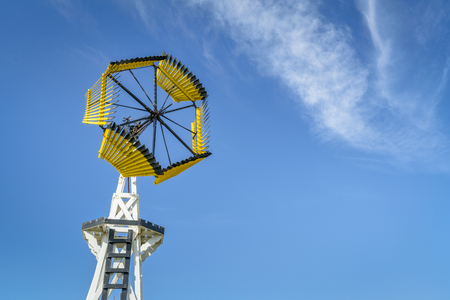 Antique windmill for water pumping in Amercian prairie against blue sky