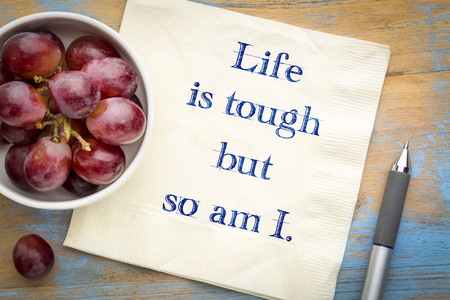 Life is tough, so am I - positive affirmation. Hnadwriting on a napkin with grapes.