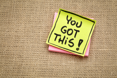 You got this! Handwriting on a sticky note against burlap canvas.