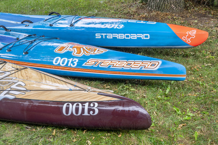 Fort Collins, CO, USA - June 30, 2018: Three stand up paddleboards by Starboard (two blue racing and expedition one) on a grass in a backyard after water rinse.