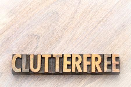clutterfree - word abstract in vintage letterpress wood type printing blocks against wooden background with a copy space