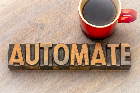 automate - word abstract in vintage letterpress wood type with a cup of coffee