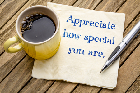 Appreciate how spaecial you are - handwriting on a napkin with a cup of coffee