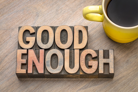 Good enough - word abstract in vintage letterpress wood type with a cup of coffee