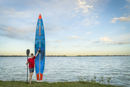 Loveland, CO, USA - May 31, 2018: A senior paddler with his racing stand up paddleboard by Starboard on a shore of Boyd Lake after sunset workout.