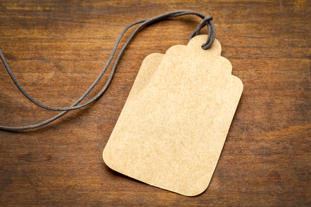 blank paper price tag with a long twine against grained rustic wood 스톡 콘텐츠
