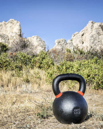 outdoor fitness concept - heavy iron kettlebell with a rock formation in background Stock Photo