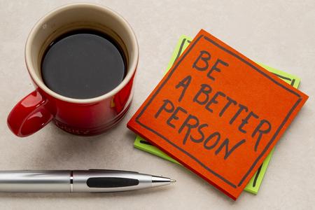 es una persona de mejor recordatorio - escritura a mano en una nota adhesiva con una taza de café