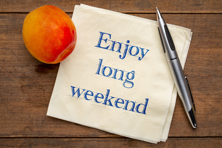 enjoy long weekend - handwriting on a napkin with a fresh apricot Banco de Imagens
