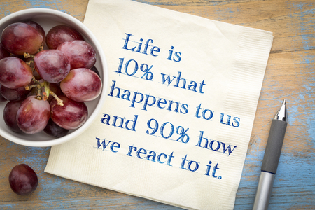 Life is 10% what happens to us and 90% how we react to it - inspiarational handwriting on napkin. Stock Photo