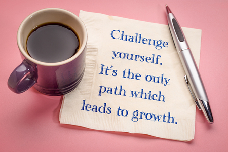 Challenge yourself, it is the only path which leads to growth - inspirational handwriting on a napkin with a cup of coffee