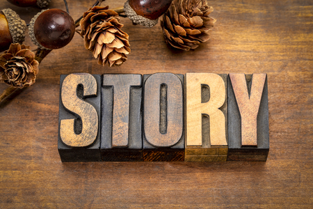 Story -  word in vintage letterpress printing blocks against rustic wood with fall decoration