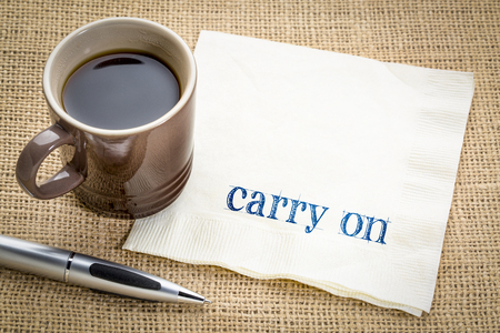 Carry on encouragement - handwriting on a napkin with a cup of coffee Banco de Imagens