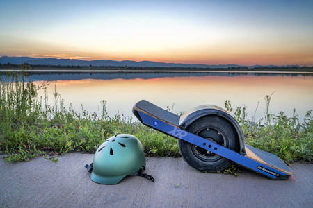 Fort Collins, CO, USA - August 11, 2018:  OneWheel electric skateboard  with a helmet on a lake sore against sunset sky. Editoriali
