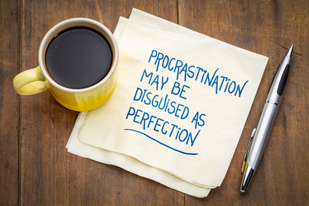 Procrastination may be disguised as perfection - inspirational handwriting on a napkin with a cup of coffee Stockfoto