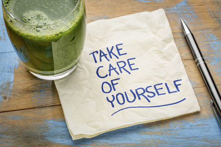 Take care of yourself - inspirational handwriting on a napkin with a glass of green juice Stock Photo