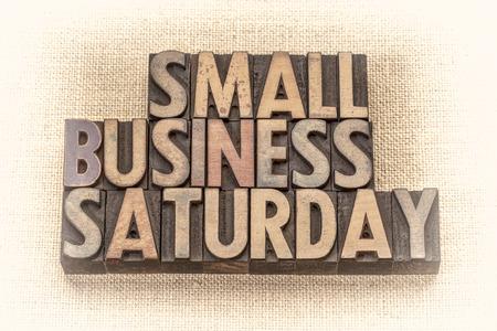 Resumen de palabras de sábado de pequeñas empresas - texto en tipografía de madera de época contra el lienzo de arpillera, imagen en tonos sepia - concepto de compras navideñas