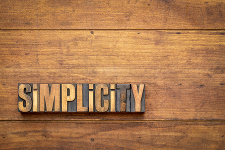 Simplicity word abstract in vintage letterpress wood type blocks against grunge wooden background with a copy space