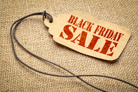 Black Friday sale sign - a paper price tag with a twine against burlap canvas