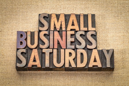 Small Business Saturday word abstract - text in vintage letterpress wood type against burlap canvas, holiday shopping concept
