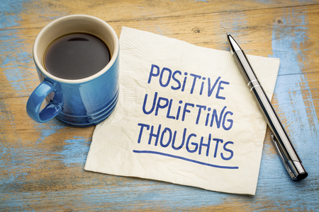 Positive, uplifting thoughts - handwriting on a napkin with a cup of espresso coffee
