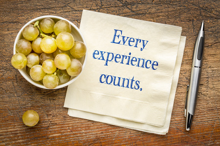 Every experience counts reminder - handwriting on a napkin with fresh grapes