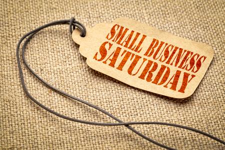 Signo de sábado para pequeñas empresas: una etiqueta de precio de papel con un cordel contra un lienzo de arpillera