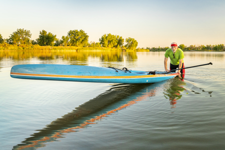 Senior male paddler with a racing stand up paddleboard on a calm lake in northern Colorado, summer scenery Stock Photo