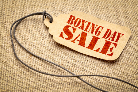 Boxing day sale sign  - a paper price tag with twine on burlap canvas - shopping concept