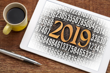 2019 number in vintage wood letterpress priniting blocks surrounded by random metal numbers on a digital tablet with a cup of coffee