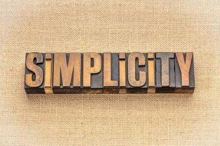 Simplicity word abstract in vintage letterpress wood type blocks against burlap canvas