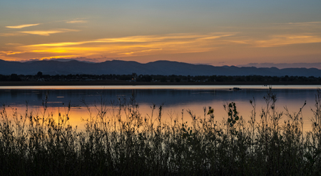 Sunset over Fronts Range of Rocky Mountains with one of numerous lakes in northern Colorado