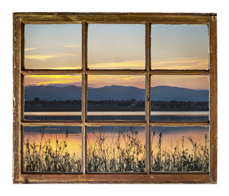 sunset over Fronts Range of Rocky Mountains with one of numerous lakes in northern Colorado as seen  through vintage, grunge, sash window with dirty glass