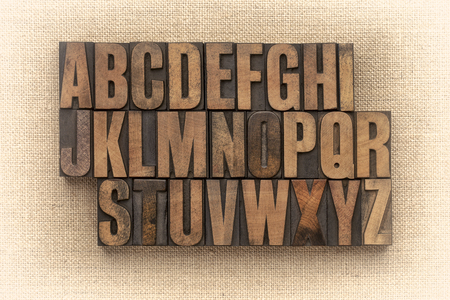 Alphabet abstract in vintage wood type against burlap canvas, sepia toned image