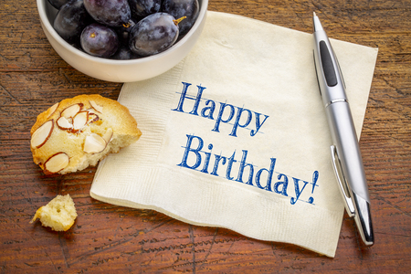 Happy Birthday greeting - handwriting on a napkin with fresh grapes and a cookie Stock Photo