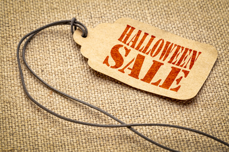 Halloween sale  - a paper price tag with a twine iagainst burlap canvas Stock Photo
