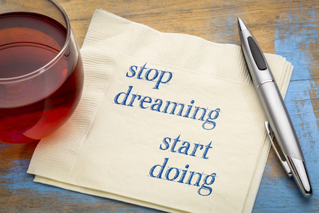 Stop dreaming, start doing - inspirational handwriting on a napkin with a cup of tea