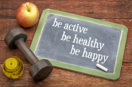 Be active, be healthy, be happy   inspiurational concept -  slate blackboard sign against weathered red painted barn wood with a dumbbell, apple and tape measure