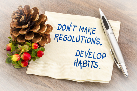 Do not make resolutions, develop habits. Handwriting on a napkin with a season decoration.