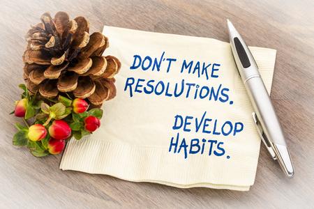 Treffen Sie keine Vorsätze, entwickeln Sie Gewohnheiten. Handschrift auf einer Serviette mit einer Jahreszeitdekoration.
