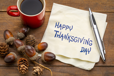 Happy Thanksgiving Day - handwriting on a napkin with a cup of coffee and fall decoration
