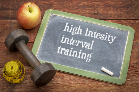 High intensity interval training  -  slate blackboard sign against rustic wood with a dumbbell, apple and tape measure