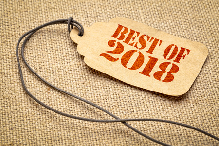 Best of 2018 sign - a paper price tag with a twine iagainst burlap canvas Stock Photo