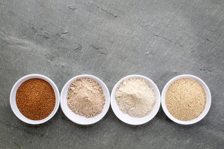 Gluten free teff grain and flour, ivory and brown variety, row of small bowls against slate stone with a copy space