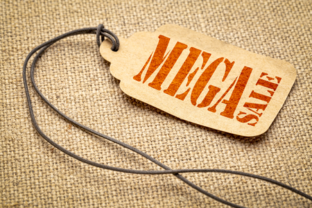Mega sale sign - a paper price tag with a twine against burlap canvas Stock Photo
