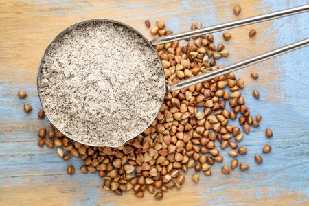 Measuring scoop of gluten free  buckwheat flour with kasha grain against wooden background