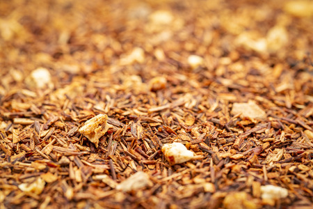 Background texture of roosts tea with cinnamon, orange peels, and clove, selective focus
