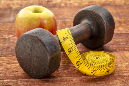 Vintage rusty iron dumbbell with a tape measure and apple on grained wood background - fitness concept